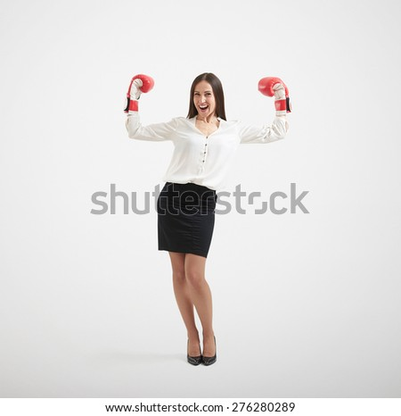 full length portrait of smiley businesswoman in formal wear and red boxing gloves raising her hands up and looking at camera over light grey background - stock photo