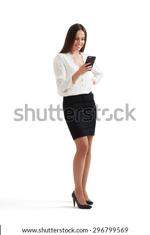 full-length portrait of smiley businesswoman in formal wear looking at smartphone. isolated on white background - stock photo