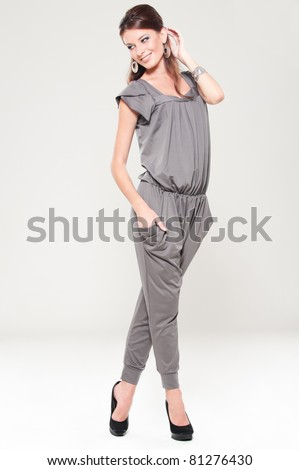 full length portrait of smiley stylish woman over grey background - stock photo