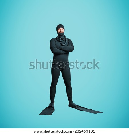 full length portrait of smiley underwater diver in equipment over blue background - stock photo