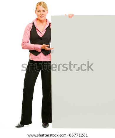 Full length portrait of smiling business woman pointing on blank board isolated on white - stock photo