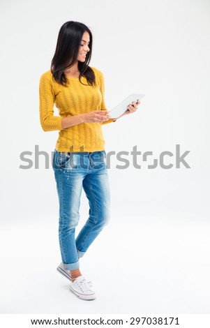 Full length portrait of smiling casual woman using tablet computer isolated on a white background - stock photo