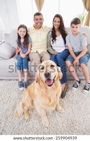 Full length portrait of smiling family with Golden Retriever at home - stock photo