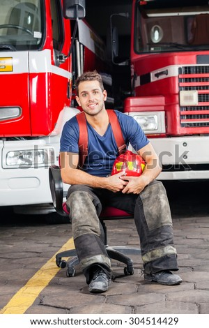 Full length portrait of smiling firefighter holding helmet while sitting against trucks at fire station - stock photo