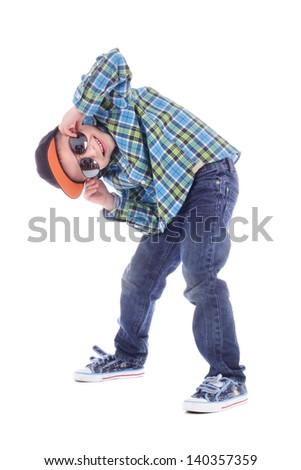 Full length portrait of smiling little boy in jeans, cup and sunglasses on white background - stock photo