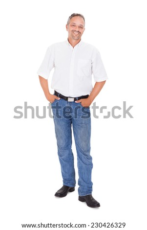 Full length portrait of smiling mature man standing with hands in pockets over white background