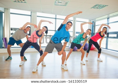 Full length portrait of smiling people doing power fitness exercise at yoga class in fitness studio - stock photo
