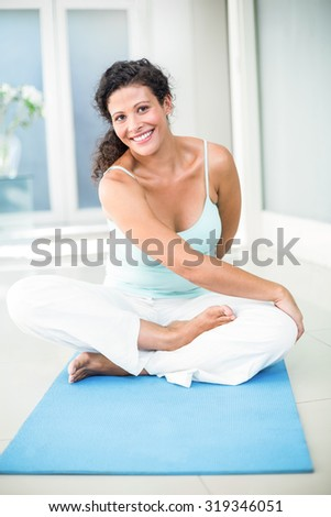 Full length portrait of smiling pregnant woman stretching while sitting on exercise mat at home - stock photo
