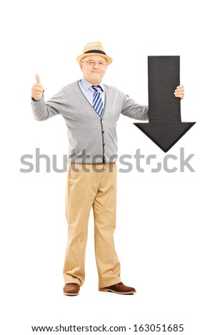 Full length portrait of smiling senior man holding a black arrow pointing down and giving a thumb up isolated on white background