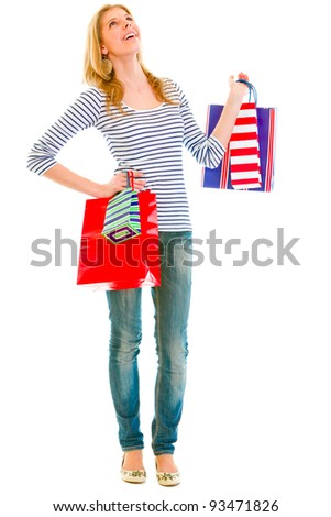 Full length portrait of smiling teen girl with shopping bags looking up