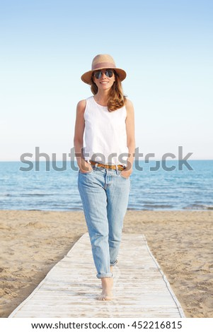 Full length portrait of smiling woman enjoying sun on vacation while walking on the beach.
