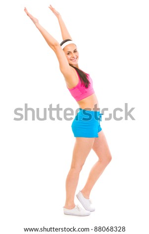 Full length portrait of smiling woman in sportswear making exercise ,