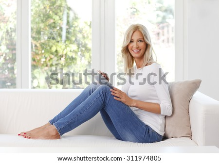 Full length portrait of smiling woman with digital tablet. Beautiful female sitting at home on sofa and touching the screen while using internet banking.  - stock photo