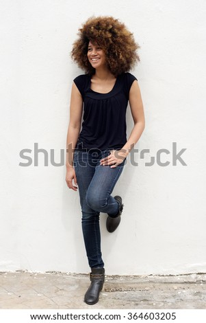 Full length portrait of smiling young african woman leaning against a white wall - stock photo