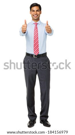 Full length portrait of smiling young businessman showing thumbs up against white background. Vertical shot. - stock photo