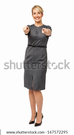 Full length portrait of smiling young businesswoman pointing at you over white background. Vertical shot. - stock photo