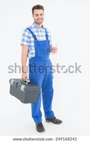 Full length portrait of smiling young male repairman carrying toolbox on white background - stock photo