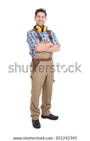 Full length portrait of smiling young male worker standing arms crossed over white background - stock photo