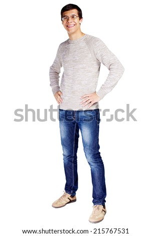 Full length portrait of smiling young man in glasses and beige sweater with hands on hips isolated on white background