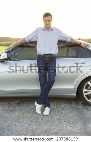 Full length portrait of smiling young man leaning on car at countryside - stock photo