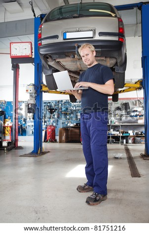 Full length portrait of smiling young mechanic using laptop in his auto repair shop - stock photo