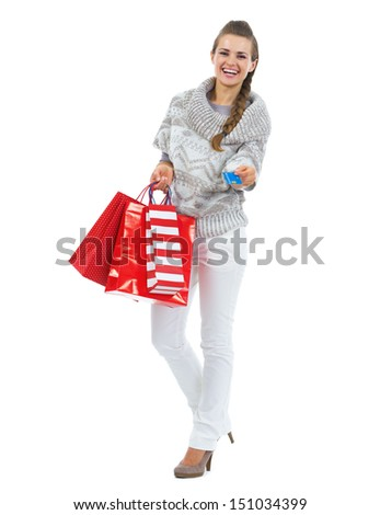 Full length portrait of smiling young woman in sweater with christmas shopping bag giving credit card