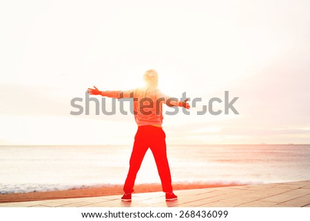 Full length portrait of sporty man raising arms towards beautiful glowing sunshine, Sport and life achievements, freedom and happiness emotional concept - stock photo
