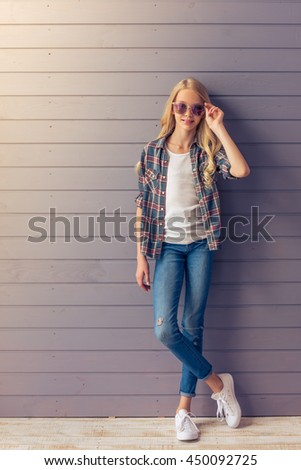 Full length portrait of stylish blonde teenage girl in casual clothes and sun glasses looking at camera and smiling while standing against gray wall - stock photo