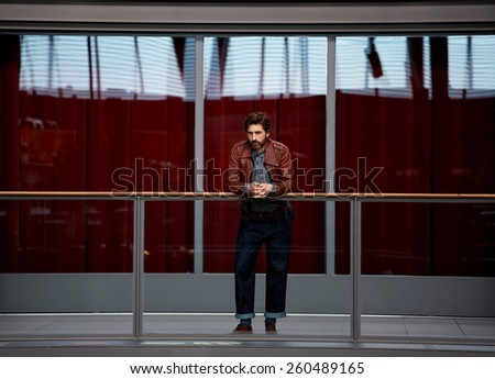 Full length portrait of stylish mature man leaning on the glass fence while standing in interior hall against red glass wall background, male clothing designer - stock photo