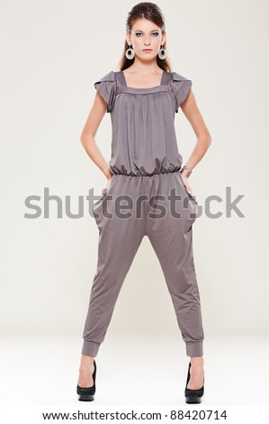 full length portrait of stylish woman over grey background - stock photo