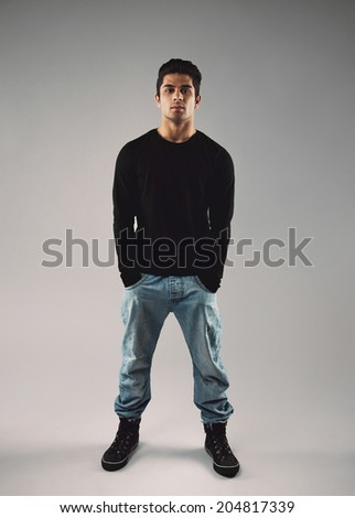 Full length portrait of stylish young man in casuals standing with his hands in pocket over grey background. - stock photo