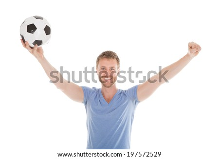 Full length portrait of successful man with arms raised holding soccer ball over white background