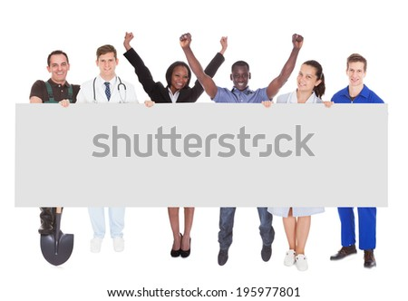 Full length portrait of successful people with different occupations holding blank billboard against white background - stock photo