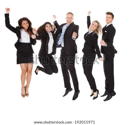 Full length portrait of successful welldressed businesspeople with arms raised standing over white background - stock photo