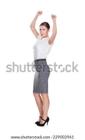 Full length portrait of successful young businesswoman standing hands raised over white background - stock photo