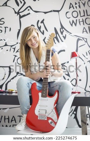 Full-length portrait of teenage girl with electric guitar sitting on study table at home - stock photo