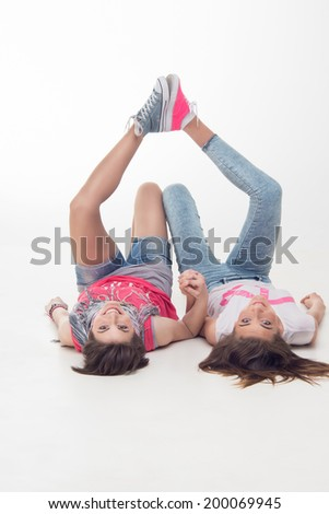 Full length portrait of teenage girls lying on the floor with their legs up. Isolated on white background. Concept of love, freedom, youth, friendship - stock photo