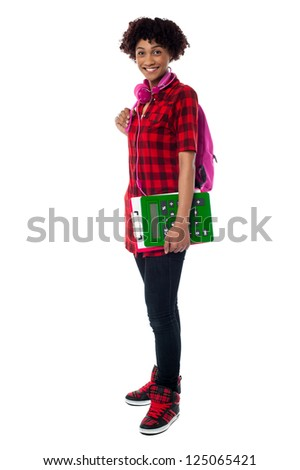 Full length portrait of teenager college student carrying back pack, clipboard and calculator.