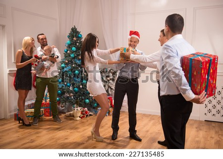 Full-length portrait of the company of happy smartly-dressed people standing in the big light cozy room with the nice New Year tree in the corner greeting each other with the holiday giving wonderful - stock photo