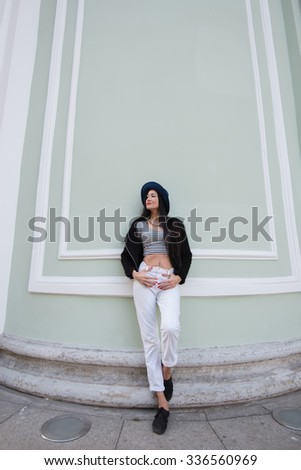 Full length portrait of the young model leaning against vintage wall with copy space area, beautiful and fashionable hipster girl posing near ancient building while dreaming about something special  - stock photo
