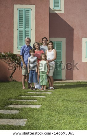 Full length portrait of three generation family in front of house - stock photo