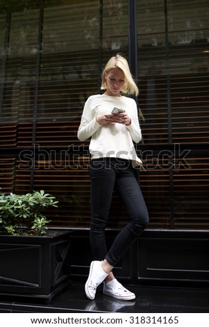 Full length portrait of trendy hipster girl chat or talk on her mobile phone while standing in the city outdoors, young female student typing a text message or browsing internet on her cellphone - stock photo