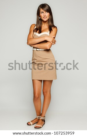 Full length portrait of trendy young woman in elegant beige dress looking to the side against gray background