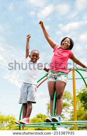Full length portrait of two African kids shouting and raising hands in park. - stock photo
