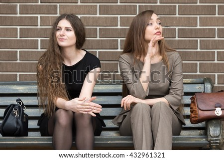Full length portrait of two beautiful young female rivals sitting side by side on bench. Attractive caucasian office women holding grudge against each other - stock photo