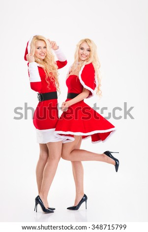 Full length portrait of two blonde beautiful sisters twins in santa claus costumes isolated over white background