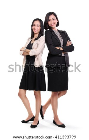 Full length portrait of two confident Asian business women wearing formal dresses, standing over white background - stock photo