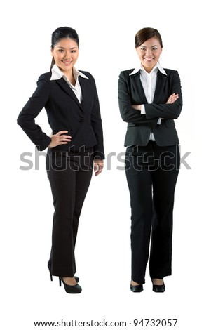 Full length portrait of two happy Asian business women - stock photo