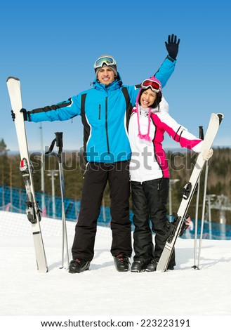 Full-length portrait of two hugging skiers with skis in hands - stock photo
