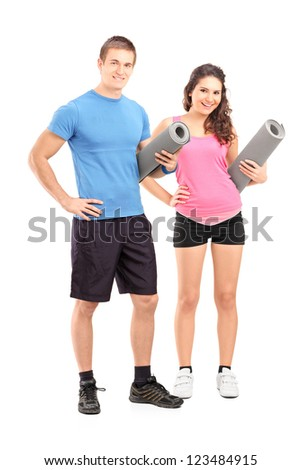 Full length portrait of two young athletes holding exercising mats isolated on white background